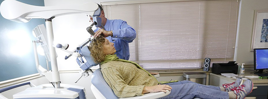 Patient sits in the chair of the NeuroStar